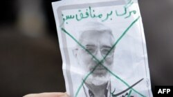 A pro-government supporter holds up a crossed-out portrait of Mir Hossein Musavi during a mass rally in Tehran last month.