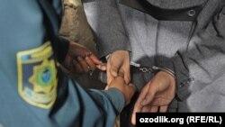 Узбекский милиционер защелкивает наручники на руках задержанного.