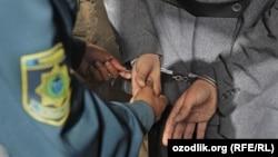 Ўзбек милиционери қўлга олинган шахсни кишанламоқда.
