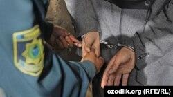 Узбекский полицейский надевает наручники. Иллюстративное фото.