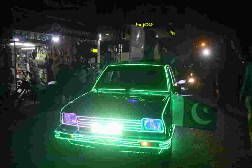 A car is lit up in green in Hyderabad.
