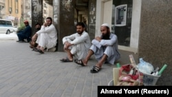 Foreign workers sit on the street after losing their jobs in May following the outbreak of the coronavirus disease in Saudi Arabia.