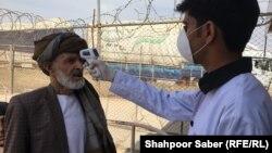 کارمند صحی افغان در مرز اسلام قلعه در حال کنترول تب یک افغان که از ایران وارد افغانستان شده است. Feb 23 2020