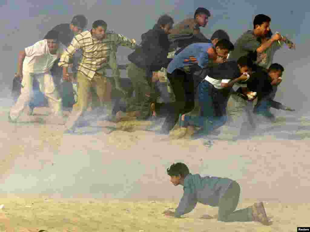 Palestinians run to escape, while one crawls, as Israeli soldiers fire teargas during Palestinian-Israeli clashes in the south Gaza Strip town of Khan Yones October 20, 2000. The ongoing conflict in Isreal has so far this year seen 281 Palestinians killed. REUTERS