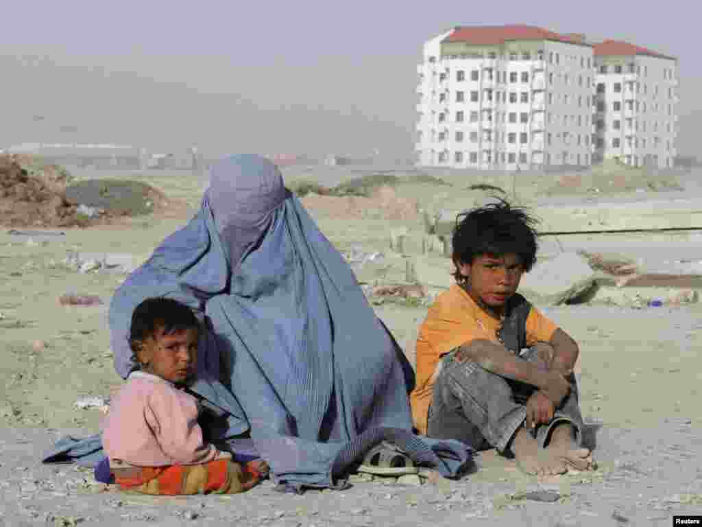 An Afghan woman dressed in a burqa begs with her children near a newly constructed building in Kabul on June 14. Photo by Mohammad Ismail for Reuters