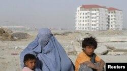 Паранжычан жакыр ооган аялы балдары менен бирге тилемчилик кылып отурат. Кабул шаары. 14.5.2011.