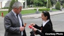 Душанбе көшесінде Георгий лентасын таратып жүрген оқушы. Тәжікстан, 7 мамыр 2012 жыл. (Көрнекі сурет)