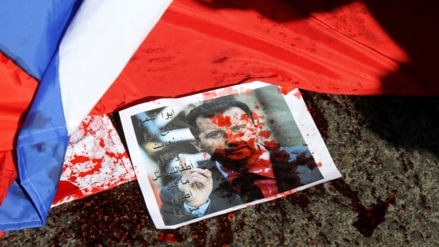 A picture of Syrian President Bashar al-Assad sprayed with red paint lies on the ground next to a Russian flag about to be set on fire by protesters during a demonstration outside the Russian Embassy in Beirut on February 5.
