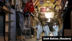 Turkey -- Workers in protective suits spray disinfectant at Grand Bazaar to prevent the spread of coronavirus in Istanbul, Turkey, March 25, 2020.