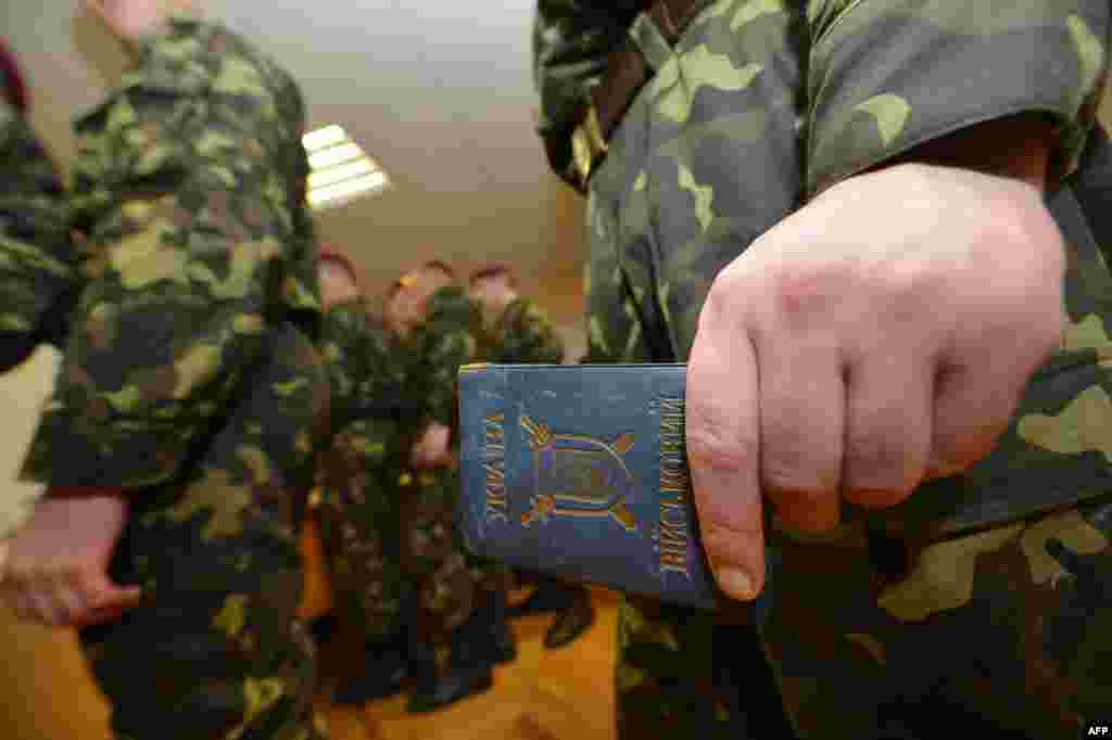 A soldier from the presidential regiment holds identification while waiting to vote in Kyiv.