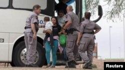 Нелегальные иммигранты из Латинской Америки выходят из автобуса Погранслужбы США в Аризоне