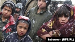 Children wait in the snow at a camp for displaced people in Kabul.
