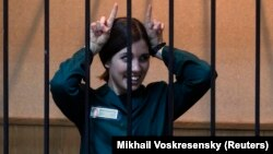 Jailed Pussy Riot member Nadezhda Tolokonnikova gestures as she looks out from a holding cell during a court hearing in April.