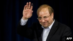 Mohammad Baqer Qalibaf waves after registering his candidacy for the June presidential election.