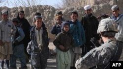A US soldier talks with Afghan children