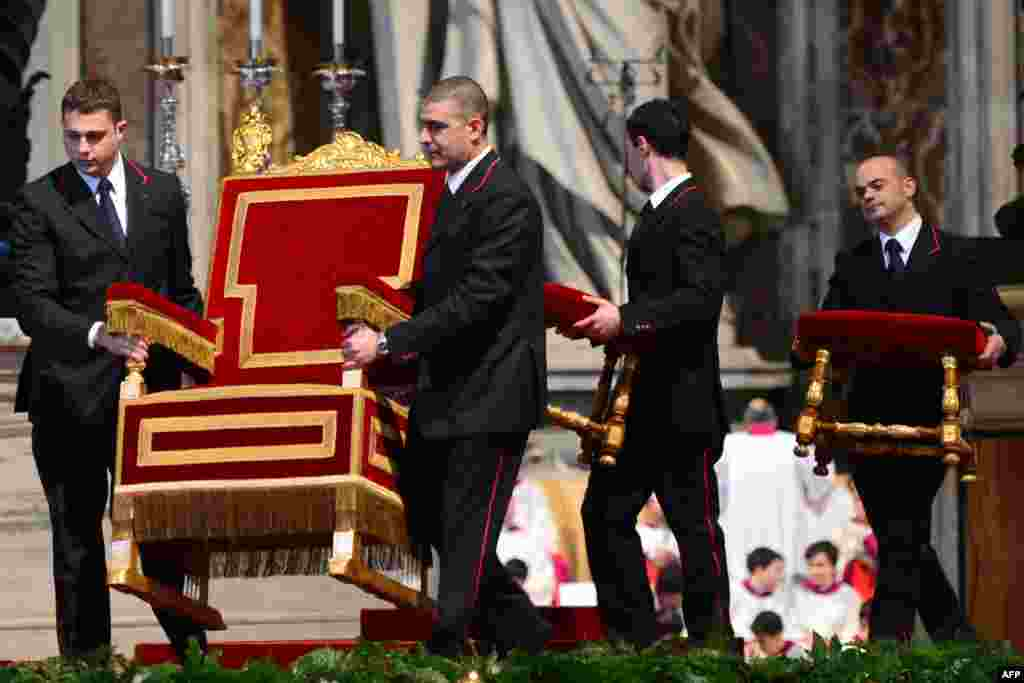 Assistants carry Pope Benedict XVI's armchair prior to a Mass on Ash Wednesday at St. Peter's basilica at the Vatican. (AFP/Gabriel Bouys)