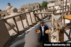 A waiter emerges from a restaurant with plates of Uzbekistan's famed plov in 2016.