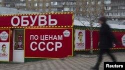 Женщина проходит мимо обувного магазина в Донецке.