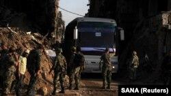 Ushtarët besnikë të Qeverisë siriane, shihen para një autobusi që bartë rebelët në afërsi të Damaskut. 30 prill, 2018