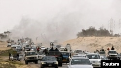 Rebel fighters flee from Ajdabiyah, on the road to Benghazi, on March 15.
