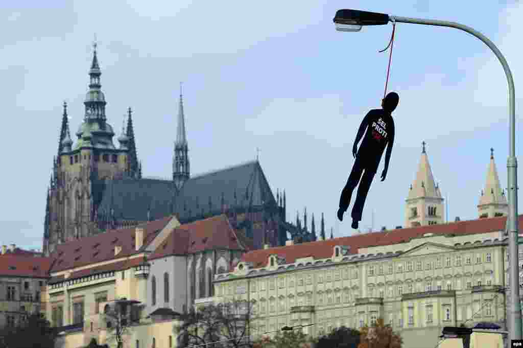 "A hanged dummy with ""Was against the Communist Party"" written on it blows in the wind with the Prague Castle in the background on October 22."