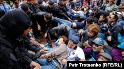 Полицейские задерживают людей на площади в центре Алматы. 9 июня 2019 года.