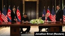 Cингапурдун Сентоса аралында АКШнын президенти Дональд Трамп жана Түндүк Кореянын лидери Ким Чен Ын документке кол коюп жатышат. 12-июнь, 2018-жыл.