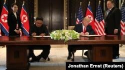 АҚШ президенті Дональд Трамп пен Солтүстік Корея басшысы Ким Чен Ын кездесу қортындысы бойынша құжатқа қол қойып отыр. Сентосa аралы, Сингапур. 12 маусым, 2018 жыл