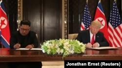 АҚШ президенті Дональд Трамп (оң жақта) пен Солтүстік Корея лидері саммит қортындысы бойынша құжатқа қол қойып отыр. Сингапур, 12 маусым 2018 жыл.