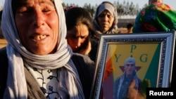 سيدة من كوباني تحمل صورة ابنها الذي قتل في المدينة