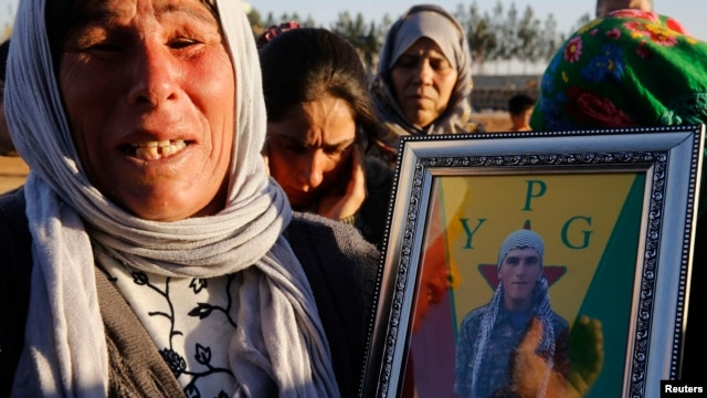 A Kurdish refugee in the Turkish town of Suruc holds a picture of her son, Merwan Imam, a YPG fighter whose body was not recovered in the battle for Kobani against Islamic State militants.