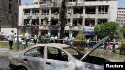 A destroyed car is pictured near a damaged building after a blast on Marjeh Square in Damascus on April 30.
