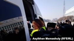 Полиция қызметкерлері наразылық акциясы өтіп жатқан жерден блогер Даная Калиеваны мәжбүрлеп әкетіп барады. Алматы, 1 наурыз 2020 жыл.