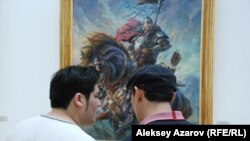 Художники Даурен Кастеев и Талгат Тлеужанов (справа) что-то обсуждают, стоя перед портретом Кабанбай-батыра кисти Даурена Кастеева. Алматы, 3 июля 2015 года.