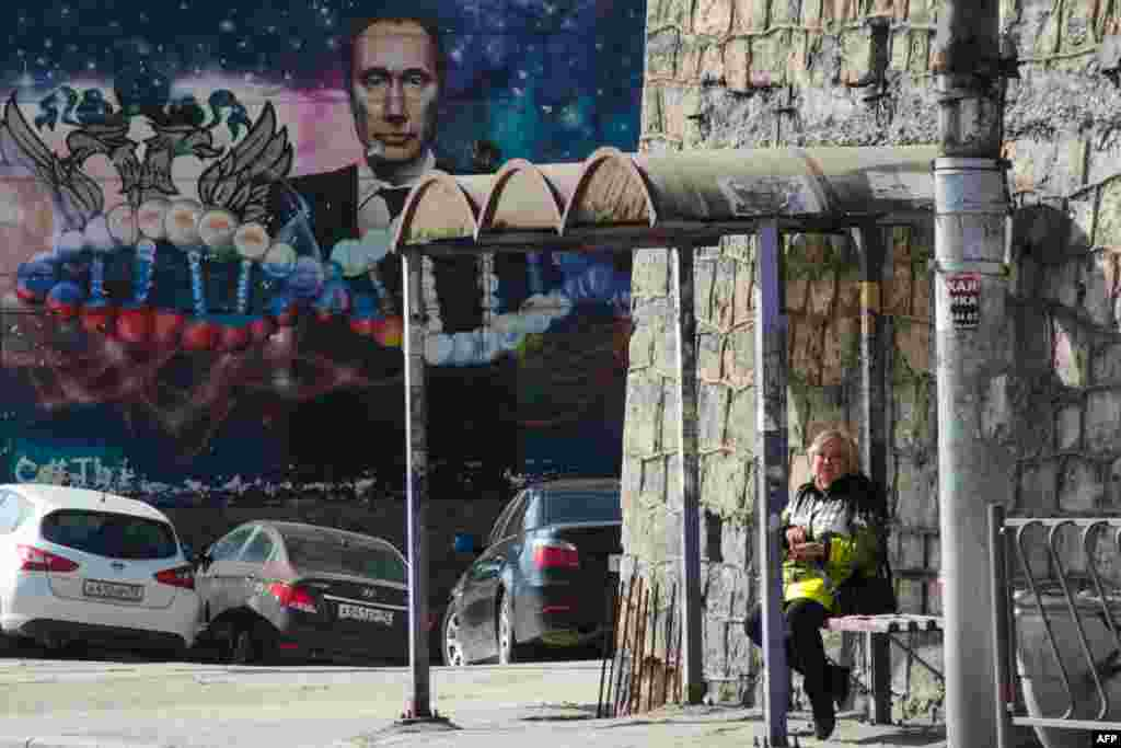 A woman waits at a bus stop in front of a graffito depicting Russian President Vladimir Putin on a building in Sevastopol on the Russian-occupied Ukrainian peninsula of Crimea. (AFP)