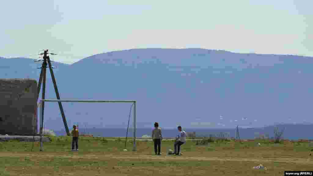 На окраине села мальчишки играют в футбол