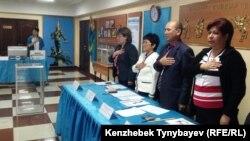 Члены избирательной комиссии слушают гимн сразу после открытия избирательного участка. Алматы, 26 апреля 2015 года.