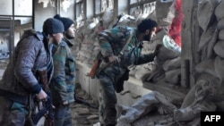 Syrian pro-government forces patrol an abandoned building in a newly retaken area of Aleppo's Old City on December 8.
