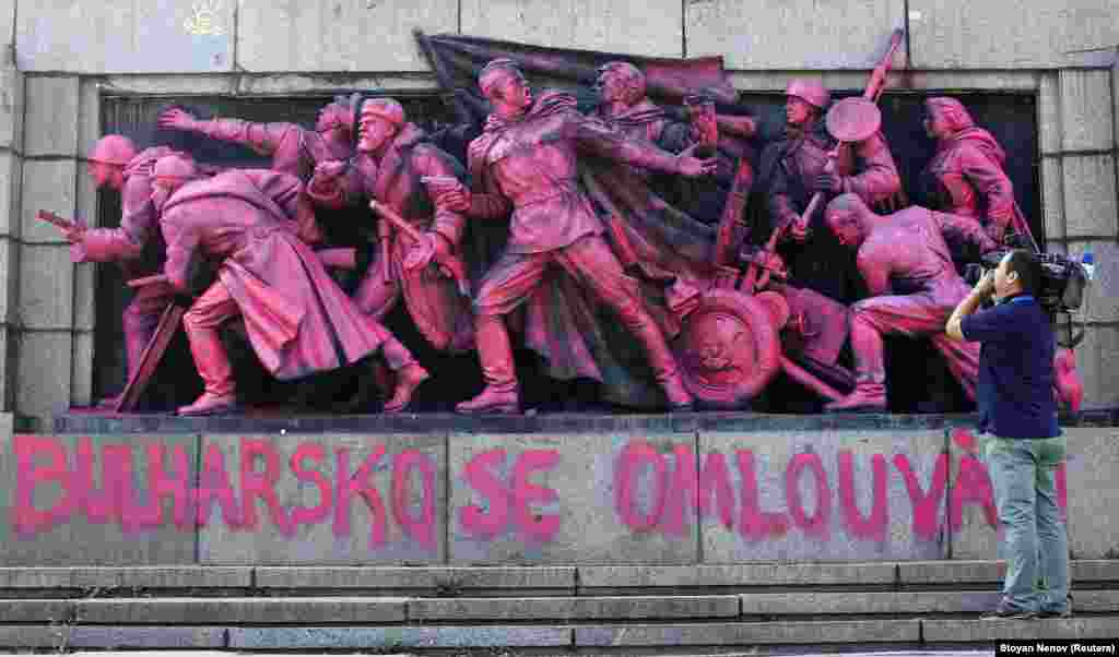 """A cameraman films the figures of Soviet soldiers at the base of the Soviet Army monument, painted pink, in Sofia. Unknown artists painted the nine soldiers pink during the night on August 21 and wrote """"Bulgaria apologizes"""" in both in the Bulgarian and Czech languages in what appears to be an artistic apology for Bulgaria's support in smashing the Prague Spring uprising against communist rule on August 20-21,1968. (Reuters/Stoyan Nenov)"""