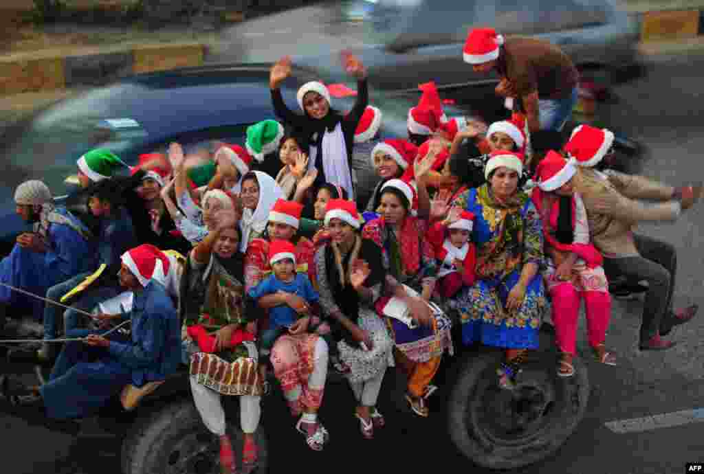 Pakistani revelers, some dressed in Santa Claus hats, take part in a camel rally in Karachi ahead of Christmas. (AFP/Asif Hassan)