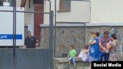 Фигурант «дела 26 февраля» Али Асанов в сопровождении полиции в Киевском райсуде Симферополя и его семья за ограждением
