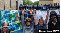 Протестующие в США подняли руки с требованием справедливости для погибшего Джорджа Флойда, в то время как полиция пустила слезоточивый газ. 27 мая 2020 года, Миннеаполис, США.
