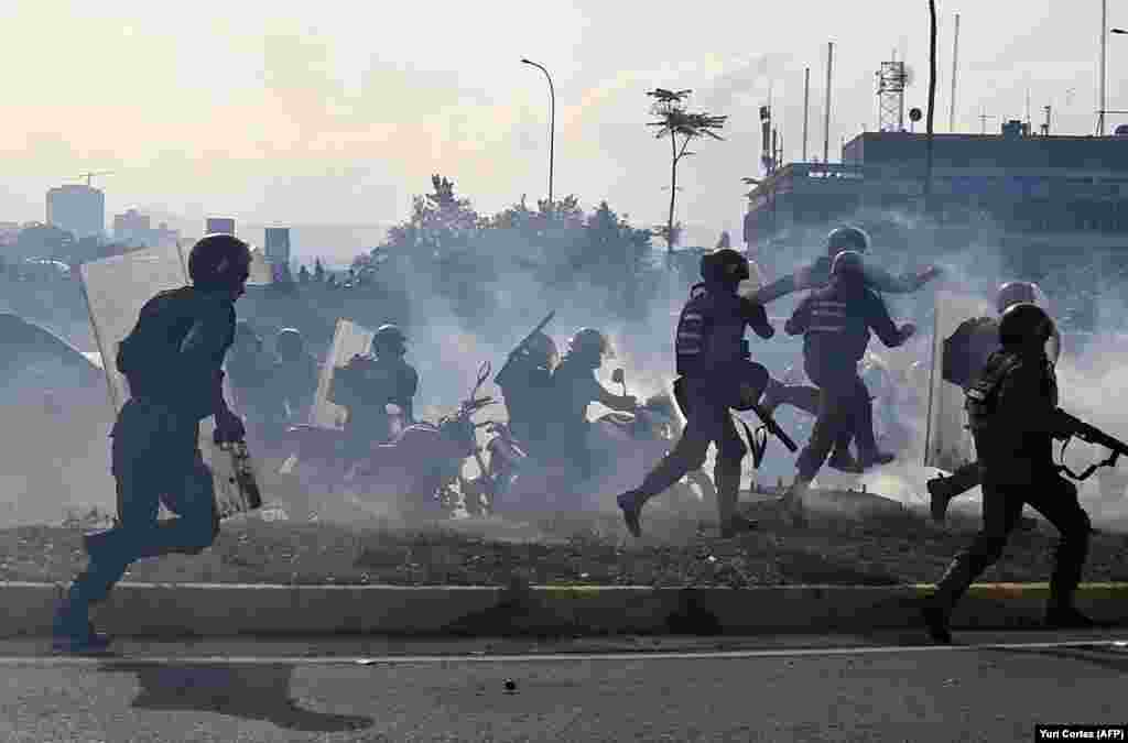 Члени Боліварської національної гвардії, вірні президенту Ніколасові Мадуро, втікають перед вогнем військових, які підтримують лідера опозиції Хуана Гуайдо, перед військовою базою Ла Карлота у Каракасі