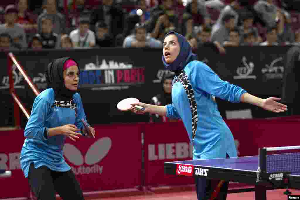 Iran's Mahjobeh Omrani (right) and Neda Shahsavari serve to Prachi Jha and Erica Wu of the United States during the women's double qualifying round at the World Team Table Tennis Championships in Paris. (Reuters/Charles Platiau)