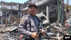 Полиция қызметкері террорлық шабуылдан қираған ғимараттың жанында тұр. Бали аралы, 13 қазан 2012 ж.