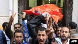 Egypt -- Egyptians transport the body of a Christian worshipper from the Al-Qiddissine (The Saints) church to an ambulance following an overnight car bomb attack on the church in the Egyptian port city of Alexandria on 01Jan11