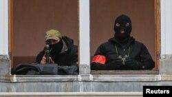 Брюссельдегі Гран-Плас терезесінен сыртты бақылап тұрған қарулы полиция қызметкерлері. Бельгия, 20 қараша 2015 жыл.