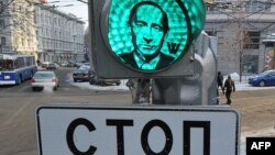 Наклейка с портретом премьер-министра России Владимира Путина, налепленная в агитационных целях на зеленый свет светофора. Москва, 13 февраля 2012 года.
