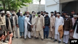 Pakistani police escort blindfolded suspects accused of killing and setting fire to a woman as they appear at a court in Abbottabad on May 5.