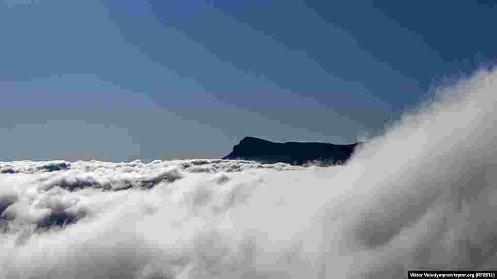 Bulutlarnıñ artında Çatır Dağ töpesini körmek mümkün